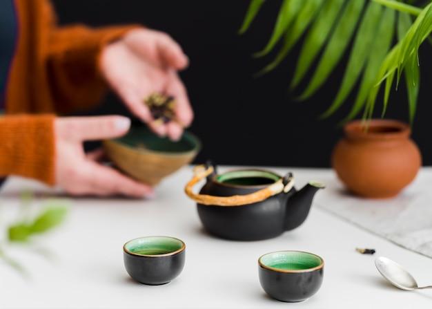 Женщина кладет травы в чай