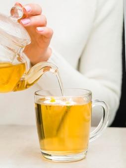 Вид спереди женщина наливает чай из хрустального чайника