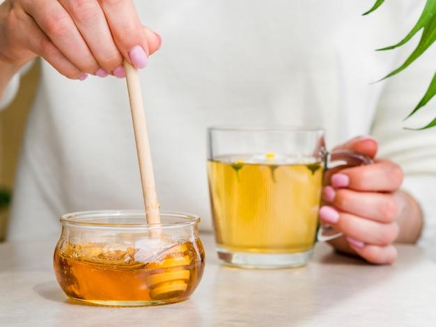 Женщина вид спереди держит стакан с чаем и ковшом в банку меда