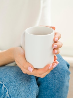 マグカップを保持しているハイアングルの女性
