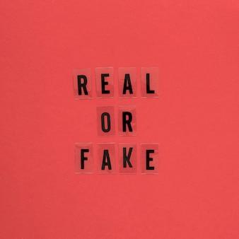 Реальные или поддельные слова черным шрифтом на красном фоне