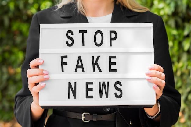 Женщина, держащая стоп поддельные новости знак