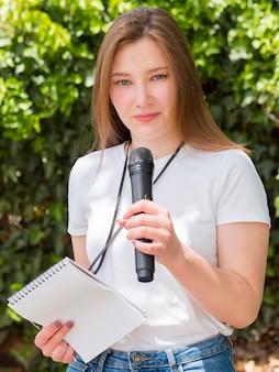 Журналистка стоит в парке
