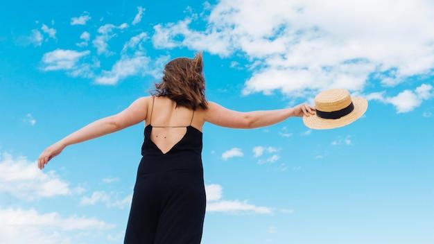 Низкий угол женщины в шляпе и небо с облаками