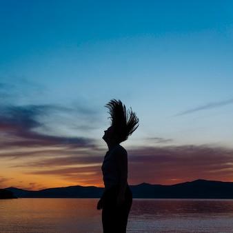 夕暮れ時のビーチで女性のシルエットの側面図