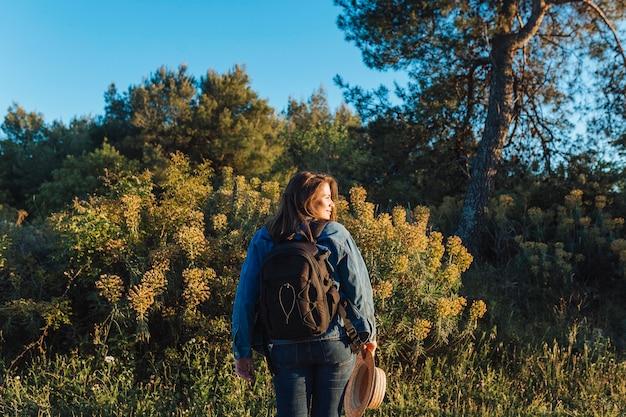 自然の中でバックパックを持つ女性の背面図
