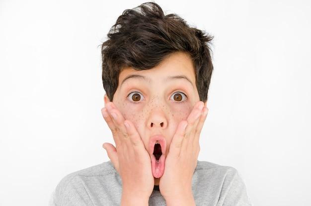 Удивленный мальчик в серой футболке