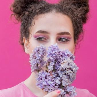 ライラック色の花で彼女の顔を覆っている若い女の子