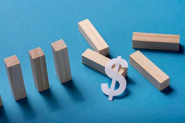 Высокий угол фигур домино со знаком доллара
