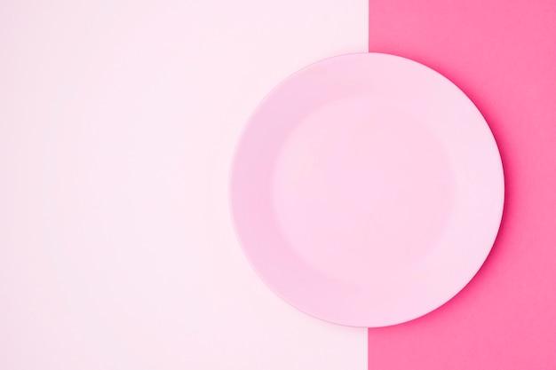 Вид сверху розовая тарелка на столе