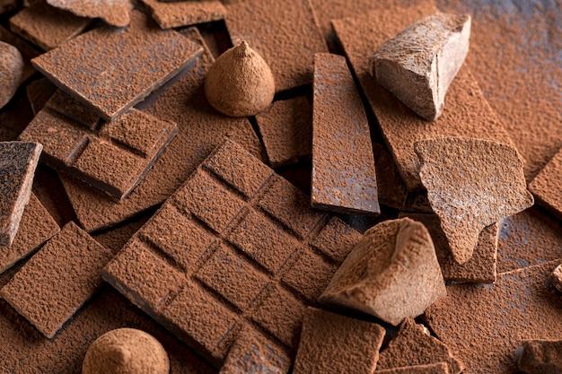 Высокий угол шоколада с конфетой и какао-порошком