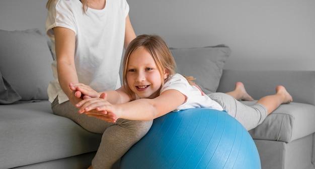 ママが女の子がボールで運動するのを助ける