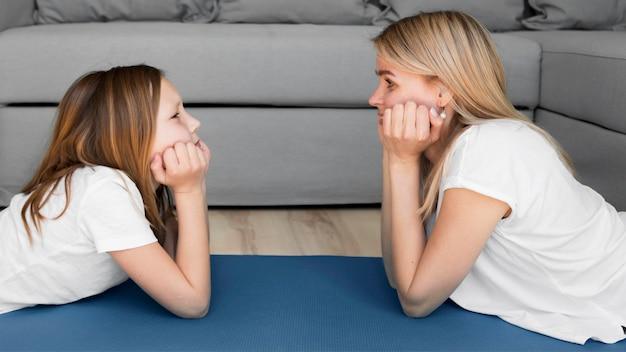 Мама и девушка тренируются на коврике