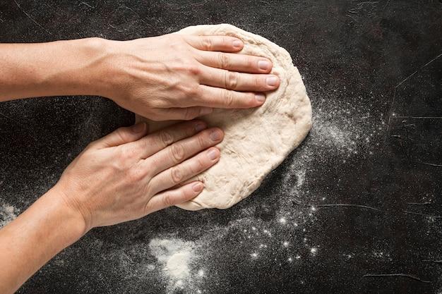 Женщина выкладывала тесто для пиццы
