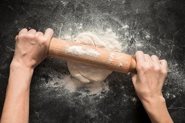 Женщина раскладывает тесто для пиццы