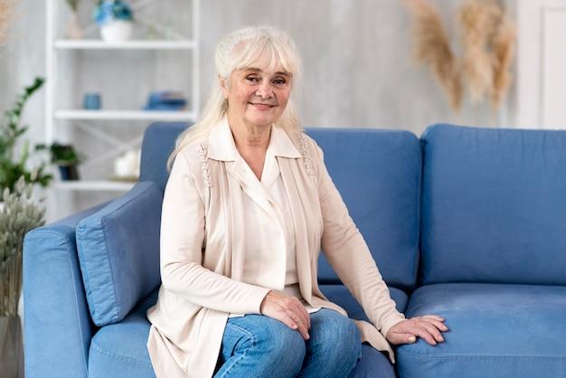 Портрет бабушки на диване у себя дома