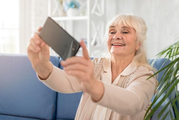 Улыбающаяся бабушка, делающая селфи
