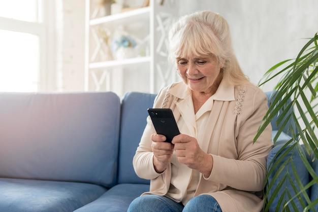 Бабушка используя мобильный телефон