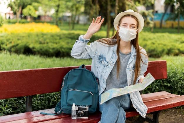 手を振っている医療マスクを身に着けている旅行者