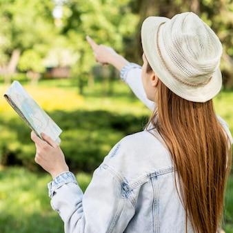 Путешественник в парке, указывая пальцем