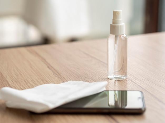 スマートフォンとナプキン付きのデスクの洗浄液