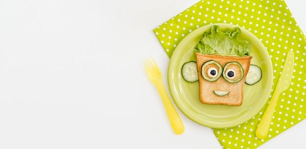 コピースペース付きのアップルとトーストの顔の形のプレート