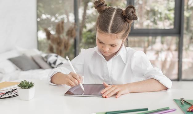 Молодая девушка учится на планшете с ручкой