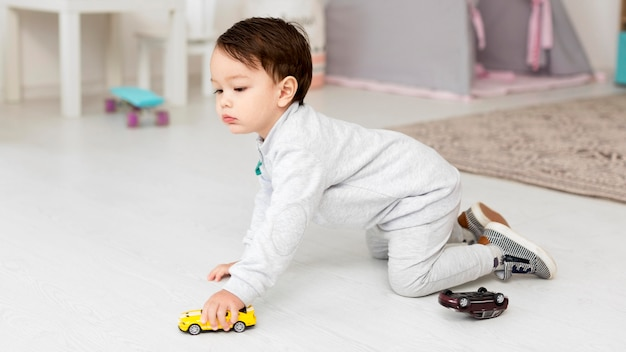 Вид сбоку малыш играет с игрушечную машинку