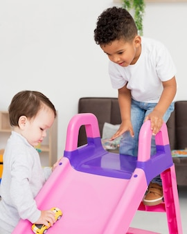 Дети играют с игрушками и горкой