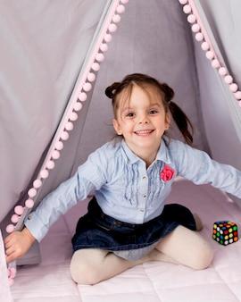 Счастливая девушка позирует в палатке дома