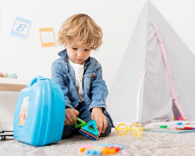 Низкий угол мальчика, играющего с игрушками дома