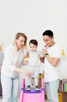 男と女が幼児がスライドを使用するのを助ける