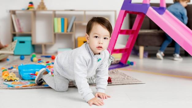 床の上でクロールの幼児の側面図