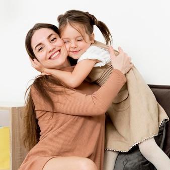 女性が幸せな若い女の子とポーズ