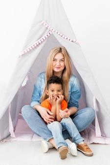 Вид спереди женщины и молодой мальчик, ставит в палатке