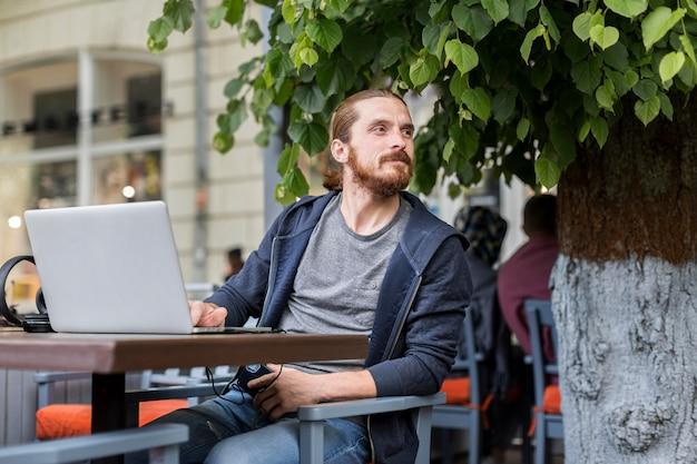 Человек с ноутбуком на городской террасе