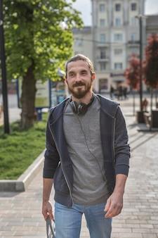 Вид спереди человека с наушниками в городе