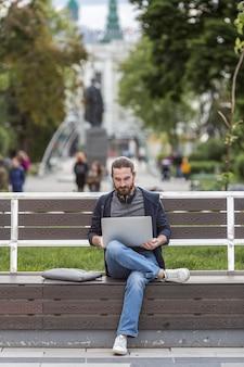 Человек сидит на скамейке и работает на ноутбуке