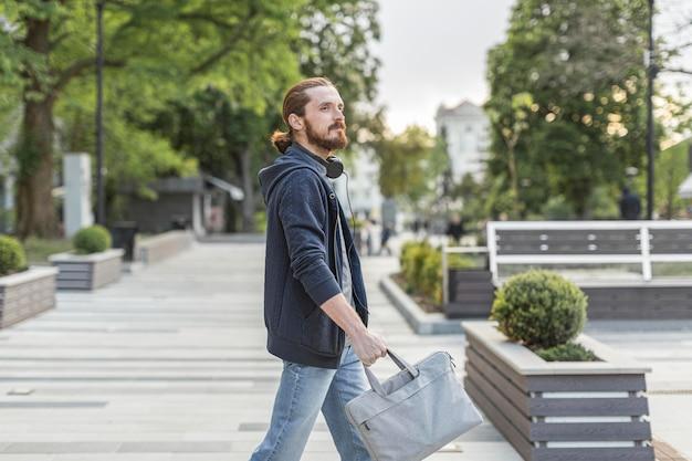 市内のラップトップバッグを持つ男の側面図