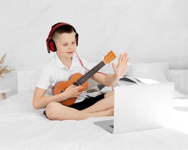 Мальчик с наушниками играет на гавайской гитаре и учится онлайн