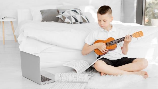 ウクレレの演奏方法に関するオンラインチュートリアルを見ている少年