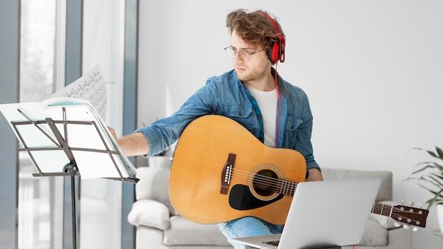 ギターを弾き、ヘッドフォンをつけている学生