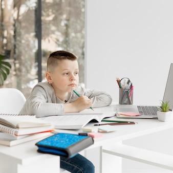 Скучающий маленький ребенок, изучающий онлайн курсы