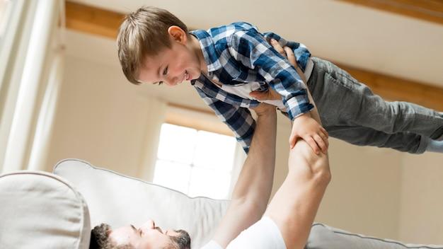Отец держит своего ребенка в воздухе