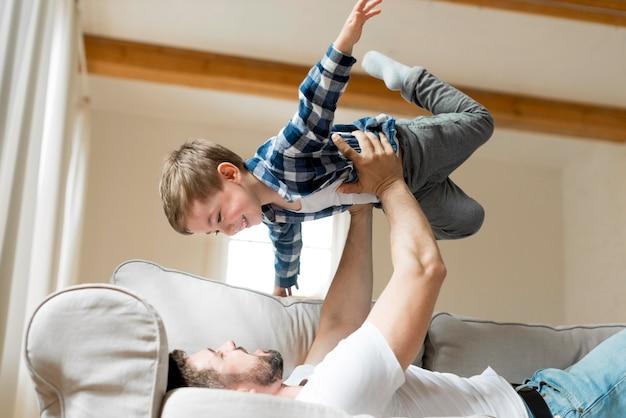 息子を宙に抱く父親