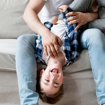 Отец вид спереди щекоча счастливого ребенка