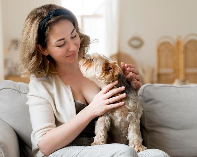 彼女のかわいい犬の正面図と遊ぶ女性