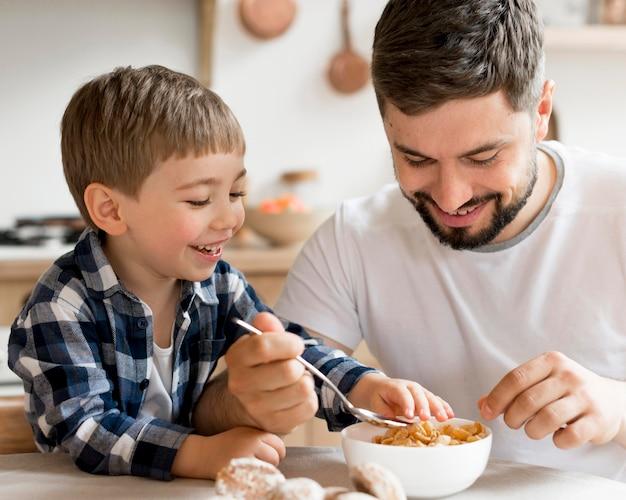 朝食にシリアルを食べる父と息子