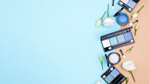 青色の背景にコピースペースを持つさまざまな化粧品の品揃え