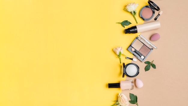 二色の背景にコピースペースを持つさまざまな化粧品の配置